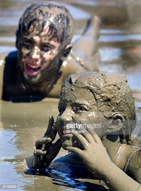 Sorrell McGill of Westland Michigan shows her mother her mudcovered face during the annual Mud Day celebration July 8 2003 in Westland Michigan...