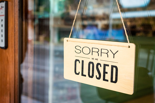 Sorry we are closed sign board hanging on door of cafe 1130208883