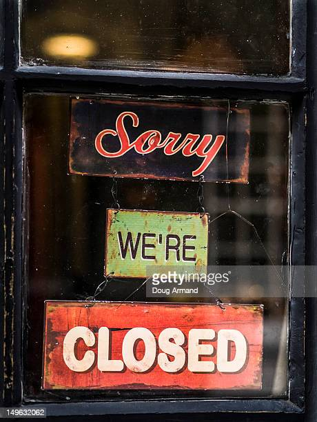 'Sorry we're closed', old signs in a shop window