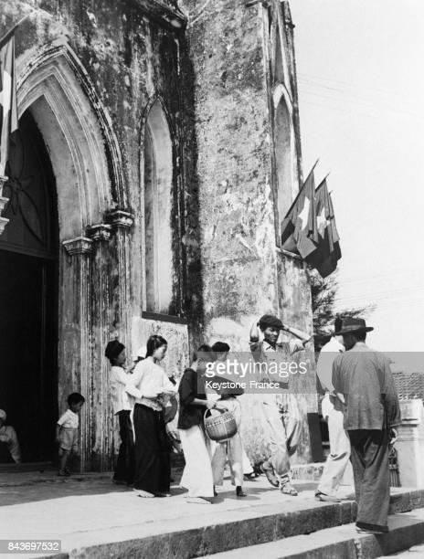 Sortie de la messe à la cathédrale de Hanoï Viêt Nam le 3 novembre 1954 Les drapeaux communistes ornent la façade