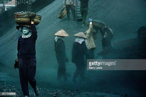 Sorting the grades of coal using a shaker Women with the sorted anthacite carry on their heads heavy baskets of coal though the thick coal dust The...