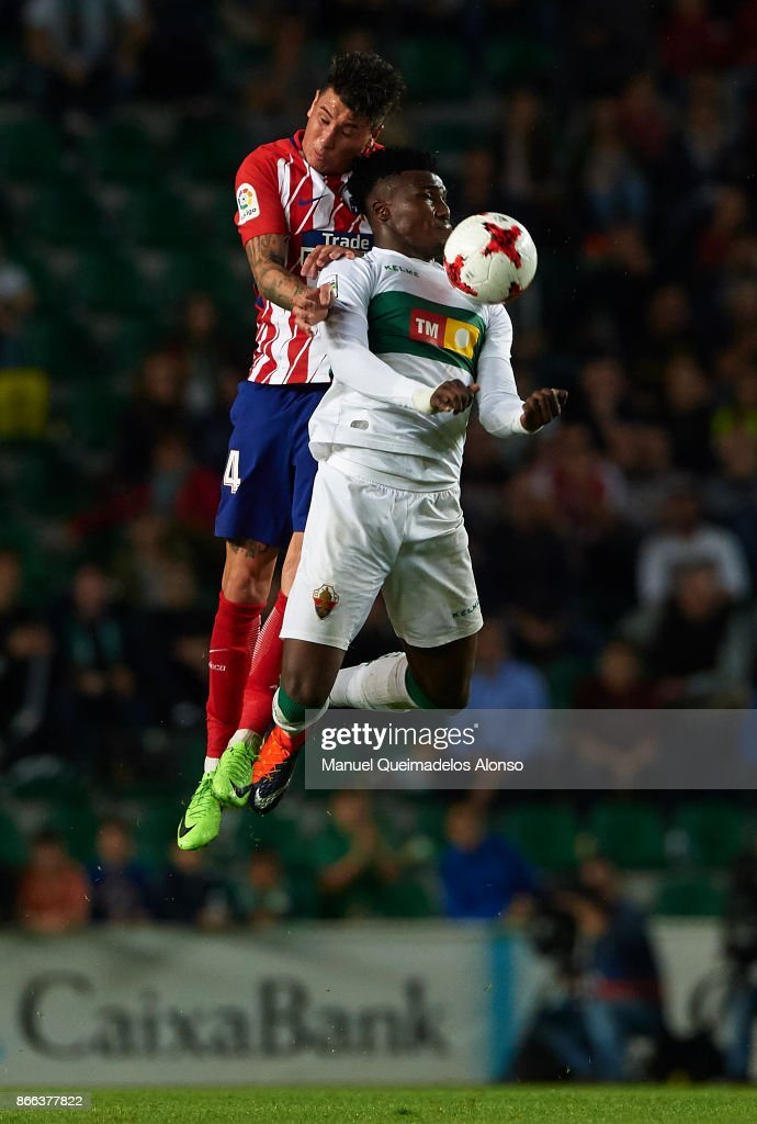 Sory Caba of Elche competes for the ball with Jose Maria Gimenez (L) of Atletico de Madrid during the Copa del Rey first leg match between Elche CF and Atletico de Madrid at Estadio Martinez Valero on October 25, 2017 in Elche, Spain.