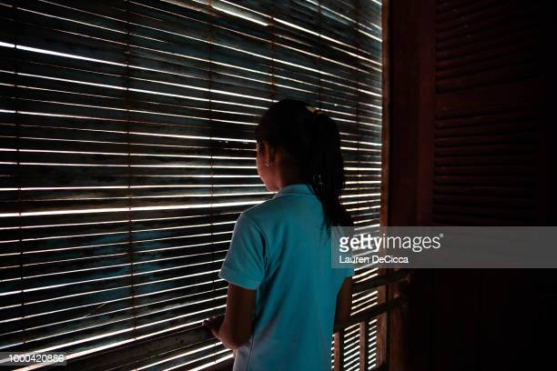 Soryia a 14 year old rape victim stands at the dormitory window of the Cambodian Women's Crisis Center shelter on July 2 2018 in Phnom Penh Cambodia...