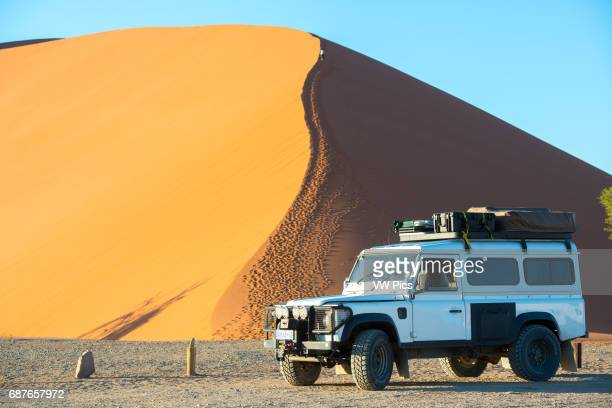 Sossusvlei Namibia Africa Land Rover Defender 110 parked in the desert with dunes in the distance