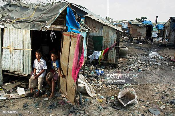 Sot and Mao Meath both 13 sit in the doorway of their family's shack atop the Steung Meanchey dump on the edge of Phnom Penh For the last three years...
