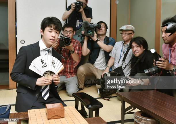 Sota Fujii youngest professional 'shogi' Japanese chess player at 14 is surrounded by reporters in Osaka on June 7 after extending his record winning...