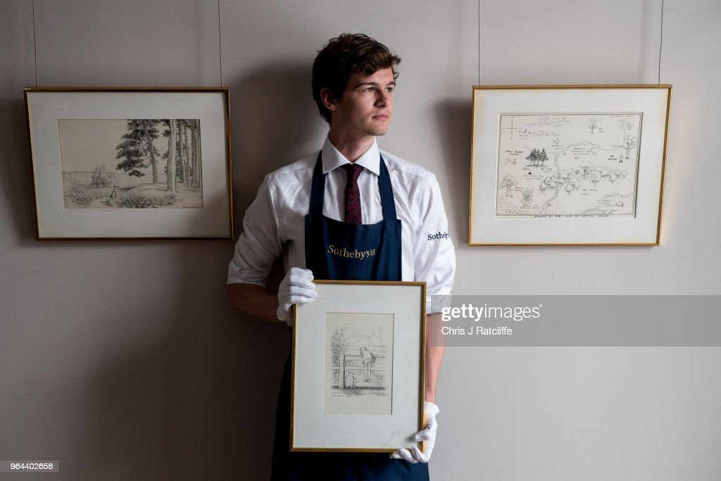 A Sotheby's art handler holds 'For a long time they looked at the river beneath them...' by E.H. Shephard, estimated at £60,000 to £80,000, next to two other original sketches at the unveiling of original Winnie-The-Pooh sketches at Sotheby's on May 31, 2018 in London, England. The map has been unseen for almost half a century and is up for sale alongside four further long hidden original Winnie-The-Pooh illustrations at Sotheby's London on 10th July 2018.