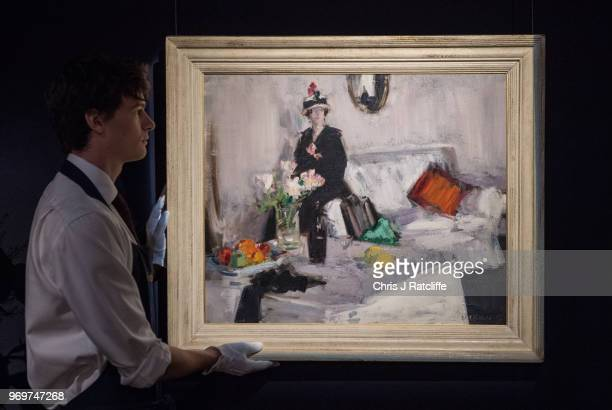 Sotheby's art handler next to Francis Campbell Boileau Cadell's 'The White Room' on view as part of Sotheby's British Art Week at Sotheby's on June 8...