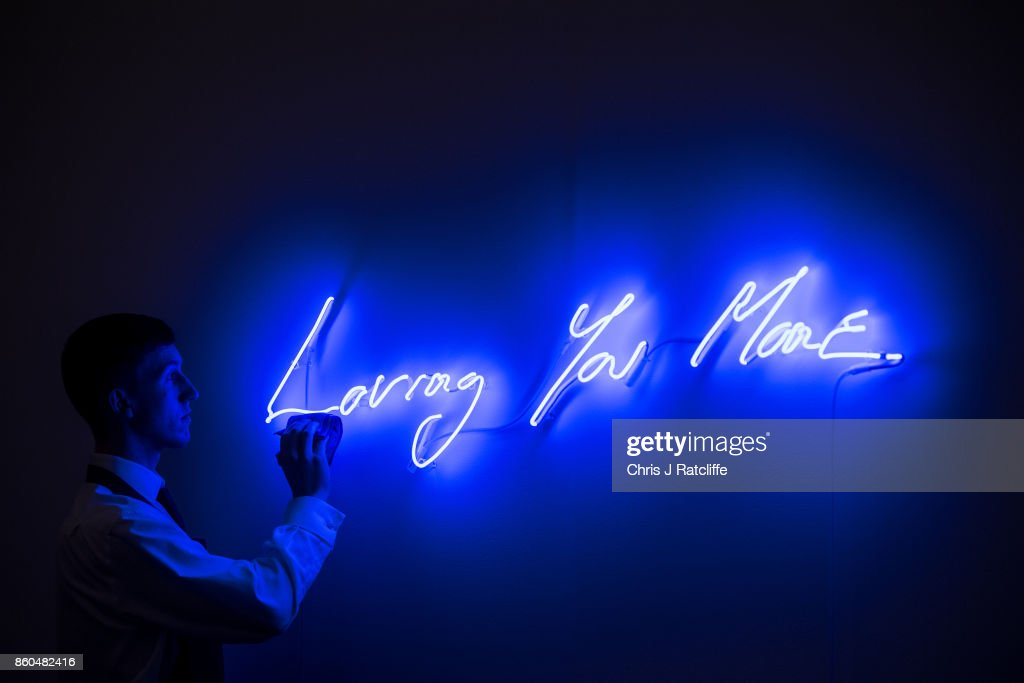 A Sotheby's art handler poses for photographs next to Loving You More by Tracey Emin, estimated at £25,000-£35,000, during an Art for Grenfell press call at Sotheby's Art for Grenfell preview on October 12, 2017 in London, United Kingdom. The 'Art for Grenfell' auction will take place on October 16 2017 and includes work by contemporary artists.
