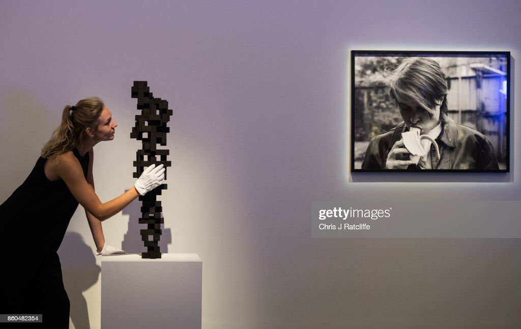 A Sotheby's art handler poses for photographs next to Small Charge by Anthony Gormley (L), estimated at £120,000-£180,000, and Eating a Banana by Sarah Lucas (R) during an Art for Grenfell press call at Sotheby's Art for Grenfell preview on October 12, 2017 in London, United Kingdom. The 'Art for Grenfell' auction will take place on October 16 2017 and includes work by contemporary artists.
