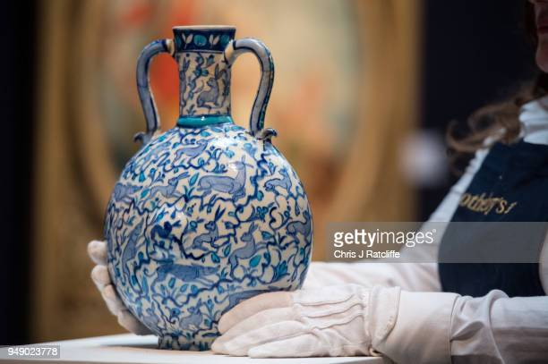 Sotheby's art handler poses with a blue and white pilgrim flask with animals during a press preview of Orientilist and Middle Eastern Art Week at...