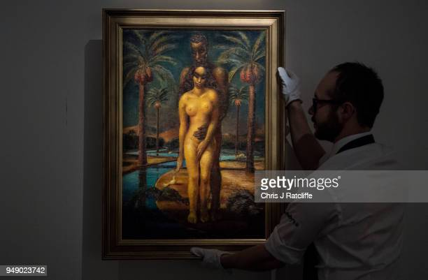 Sotheby's art handler poses with 'Adam and Eve' by Mahmoud Said during a press preview of Orientilist and Middle Eastern Art Week at Sotheby's on...