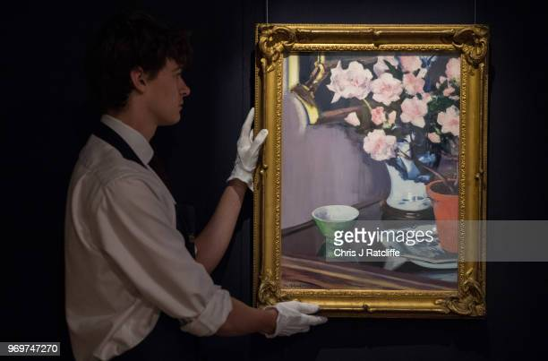 Sotheby's art handler poses with Francis Campbell Boileau Cadell's 'The Pink Azaleas' on view as part of Sotheby's British Art Week at Sotheby's on...