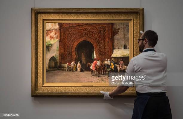 Sotheby's art handler poses with 'Rabat ' by Edwin Lord Weeks during a press preview of Orientilist and Middle Eastern Art Week at Sotheby's on April...