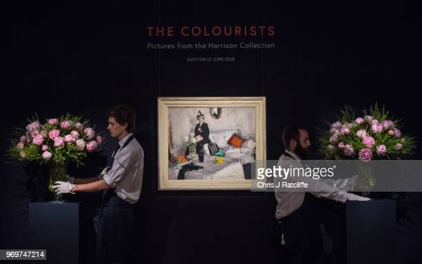 Sotheby's art handlers arrange flowers next to Francis Campbell Boileau Cadell's 'The White Room' on view as part of Sotheby's British Art Week at...