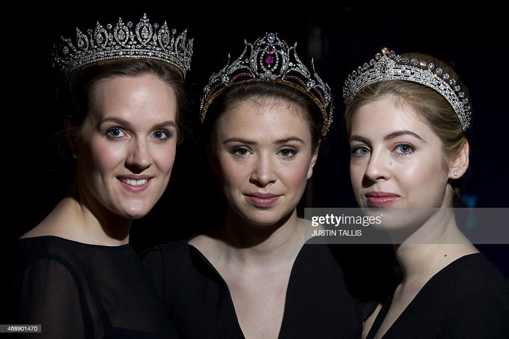 Sotheby's auction house employees pose wearing three diamond tiaras from the estate of Mary, Duchess of Roxburghe during a press preview in London on April 8, 2015. TALLIS
