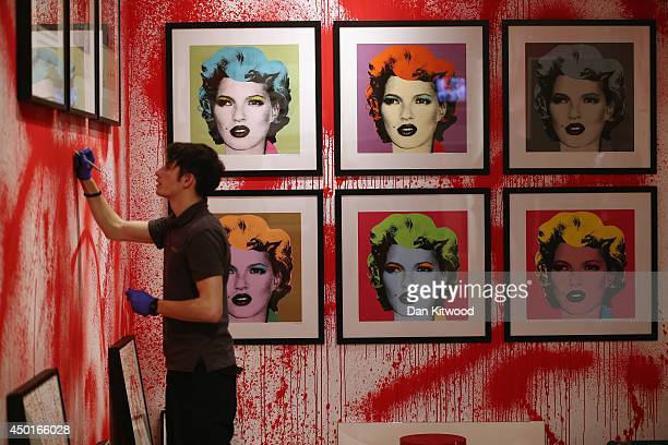 Sotheby's employee hangs a print ahead of the first unauthorized retrospective of works by UK artist Banksy on June 6, 2014 in London, England. The...