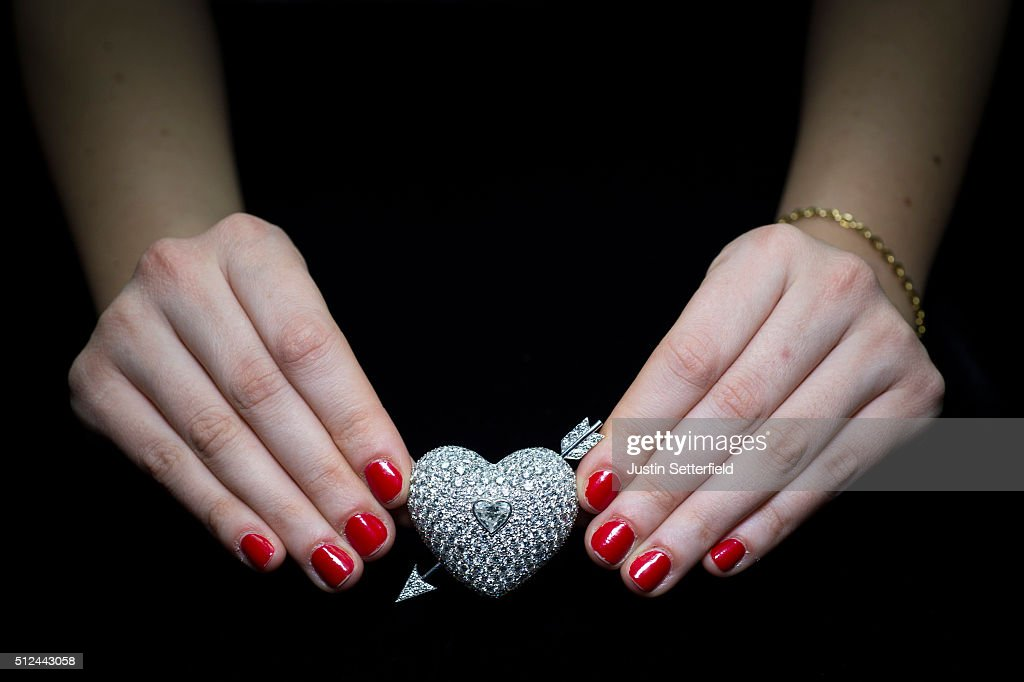 A Sotheby's employee holds a Diamond Brooch, designed by Andrew Cavendish, 11th Duke of Devonshire during the pre-auction preview of the personal collection of Deborah Cavendish, Duchess of Devonshire at Sotheby's on February 26, 2016 in London, England. The Brooch, which has the design of a heart pierced with an arrow, was presented to the Duchess by her husband to mark their Diamond Wedding Anniversary in 2001 and has an estimated auction value of £7,000-10,000. The youngest of the Mitford Sisters, and for half a century the chatelaine of Chatsworth, one of Englands greatest stately homes, Deborah Cavendish, Duchess of Devonshire was at the very heart of British rural, cultural and political life. The exhibition of her collection opens to the public on February 27, and the sale takes place on March 2, 2016.