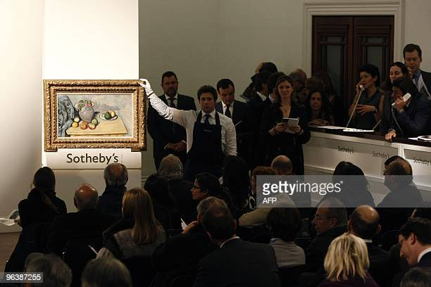 A Sotheby's employee holds a painting by French artist Paul Cezanne entitled 'Pichet et Fruits Sur une Table' after carrying it into the auction room...