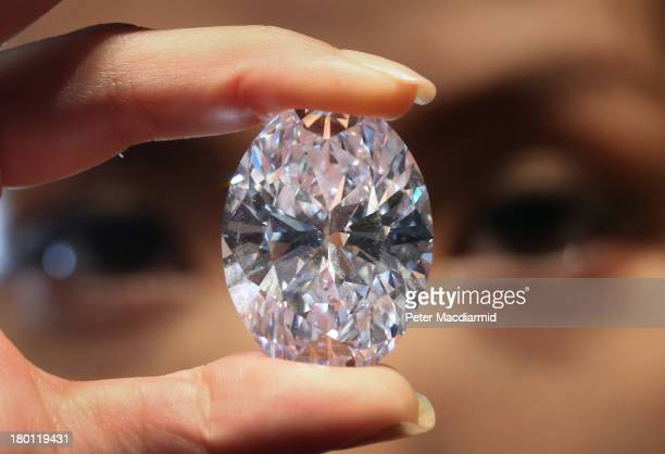 Sotheby's employee holds the largest D colour, Flawless, Type IIa white oval diamond to come to auction on September 9, 2013 in London, England. The...