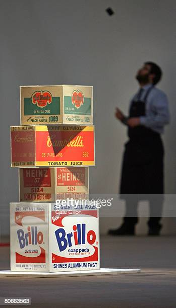 Sotheby's employee in the gallery behind Andy Warhol's 'Set of Four Boxes Brillo Box Campbell's Tomato Juice Box Del Monte Peach Halves Box Heinz...