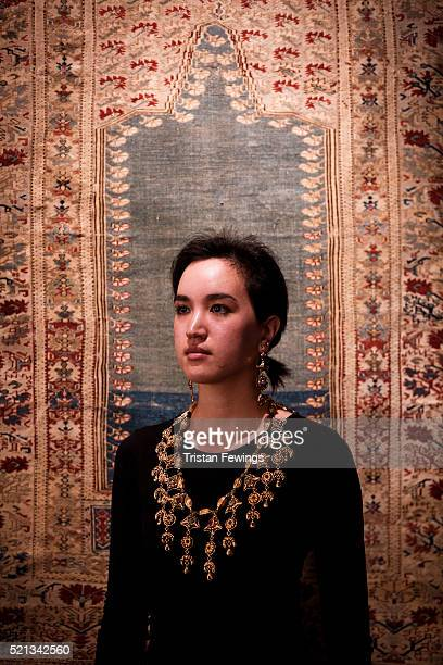 Sotheby's employee models a Moroccan gemset and enamelled gold necklace alongside a Ghiordes prayer rug at the opening of Sotheby's Orientalist and...