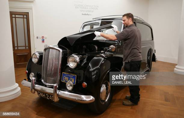A Sotheby's employee poses during a presale photocall featuring late British musician John Lennon's 1956 Austin Princess Limousine hearse with an...