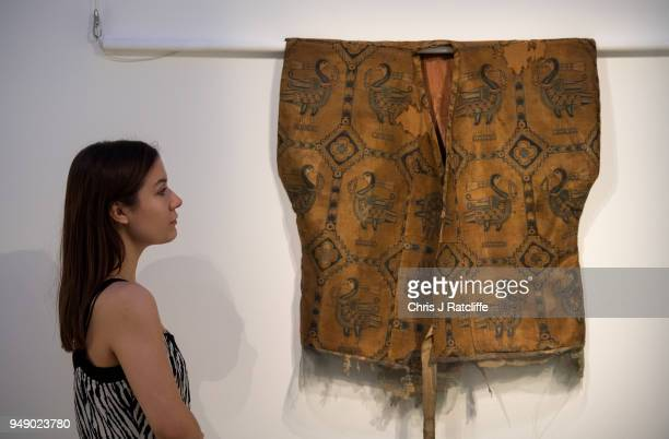 Sotheby's employee poses next to a samite shirt with ducks during a press preview of Orientilist and Middle Eastern Art Week at Sotheby's on April 20...