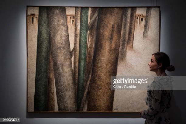Sotheby's employee poses next to 'Untitled ' by Sohrab Sepehri during a press preview of Orientilist and Middle Eastern Art Week at Sotheby's on...