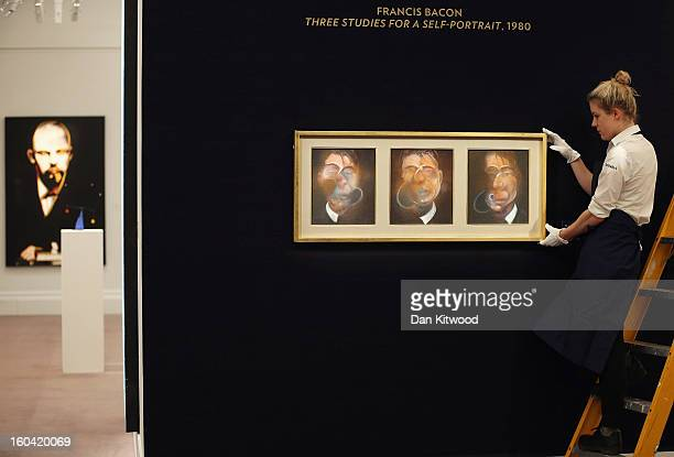 Sotheby's employee poses with a painting by Francis Bacon entitled 'Three Studies for a SelfPortrait' on January 31 2013 in London England The piece...