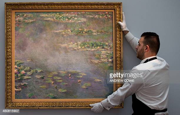A Sotheby's employee poses with a painting by late French impressionist painter Claude Monet entitled 'Nympheas' during a preview ahead of an auction...