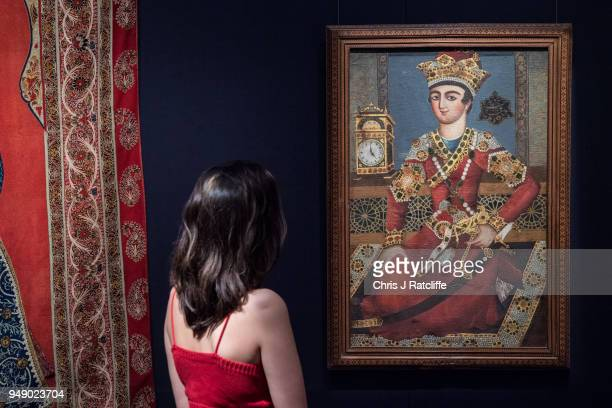 Sotheby's employee poses with 'A portraits of Khosrow Parviz' during a press preview of Orientilist and Middle Eastern Art Week at Sotheby's on April...