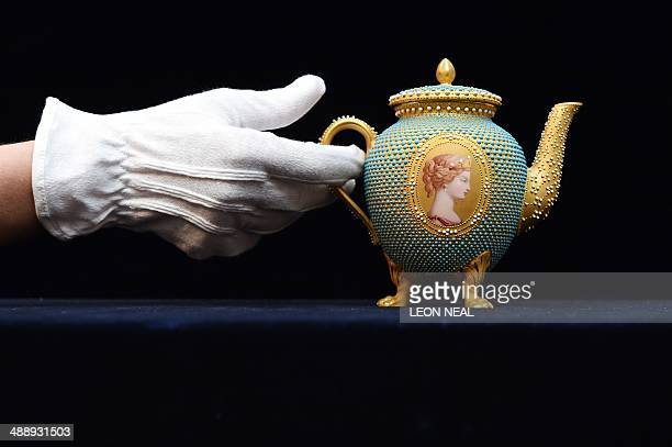 A Sotheby's employee poses with one of two Royal Worcester jewelled Coutness of Dudley service teapots at a press preview of items from the Hanley...