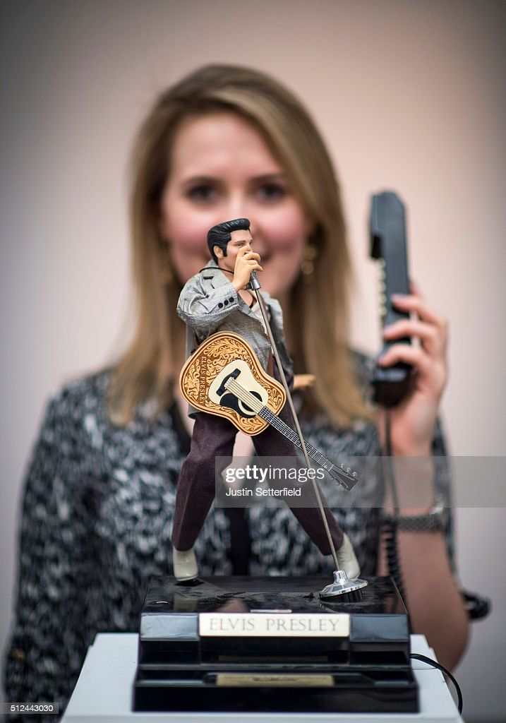 A Sotheby's employee stands behind a novelty Elvis telephone during the pre-auction preview of the personal collection of Deborah Cavendish, Duchess of Devonshire at Sotheby's on February 26, 2016 in London, England. The telephone, previously installed in the Blue Drawing Room at Chatsworth, has an estimated auction price of £500-1,000. The youngest of the Mitford Sisters, and for half a century the chatelaine of Chatsworth, one of Englands greatest stately homes, Deborah Cavendish, Duchess of Devonshire was at the very heart of British rural, cultural and political life. The exhibition of her collection opens to the public on February 27, and the sale takes place on March 2, 2016.