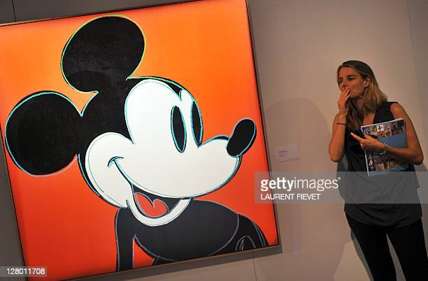 A Sotheby's employee stands by a painting by Andy Warhol entitled Mickey mouse during an auction preview in Hong Kong on September 30 2011 The...