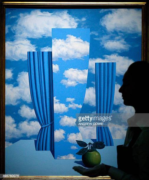 A Sotheby's employee stands in front of Rene Magritte's Le Beau Monde during the Sotheby's Impressionist Modern Contemporary Art auctions press...