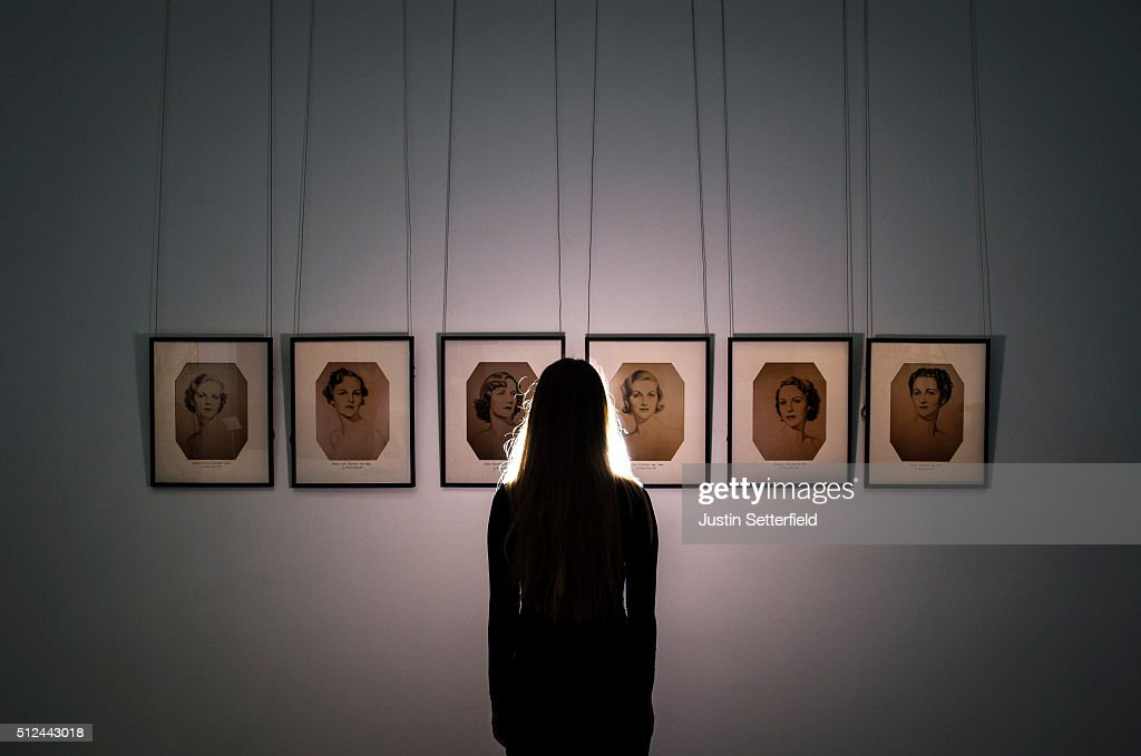 A Sotheby's employee stands infront of a series of portraits of the Mitford Sisters during the pre-auction preview of the personal collection of Deborah Cavendish, Duchess of Devonshire at Sotheby's on February 26, 2016 in London, England. The youngest of the Mitford Sisters, and for half a century the chatelaine of Chatsworth, one of Englands greatest stately homes, Deborah Cavendish, Duchess of Devonshire was at the very heart of British rural, cultural and political life. The exhibition of her collection opens to the public on February 27, and the sale takes place on March 2, 2016.