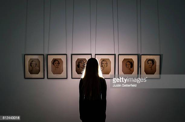 Sotheby's employee stands infront of a series of portraits of the Mitford Sisters during the pre-auction preview of the personal collection of...