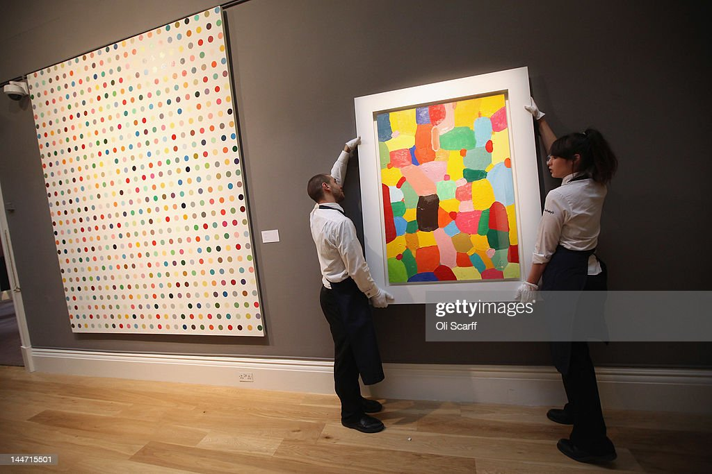 Sotheby's employees adjust a painting by Damien Hirst entitled 'Jolly' next to another work by Hirst entitled 'Chloroacetic Acid' (L) on May 18, 2012 in London, England. The artworks feature in Sotheby's forthcoming Contemporary Art sale which is to be held on June 26 and 27, 2012.