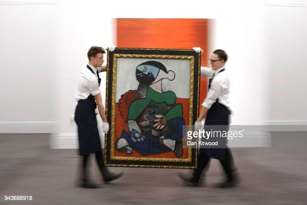Sotheby's employees carry a painting by Pablo Picasso entitled 'Femme au Chien' during a UK preview of the 'Impressionist and Modern Art' sale on...