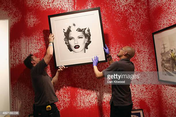 Sotheby's employees hang a print ahead of the first unauthorized retrospective of works by UK artist Banksy on June 6, 2014 in London, England. The...