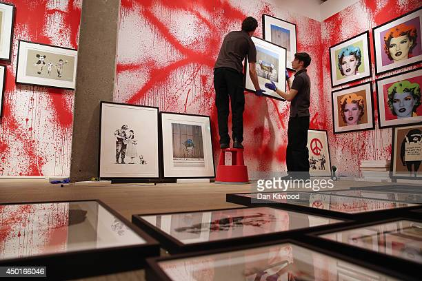 Sotheby's employees hang prints ahead of the first unauthorized retrospective of works by UK artist Banksy on June 6, 2014 in London, England. The...