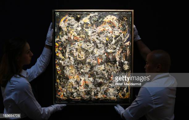 Sotheby's employees hold Jackson Pollock's 'Number 4 1951' on October 8 2012 in London England Estimated at $2535 million the work forms part of...