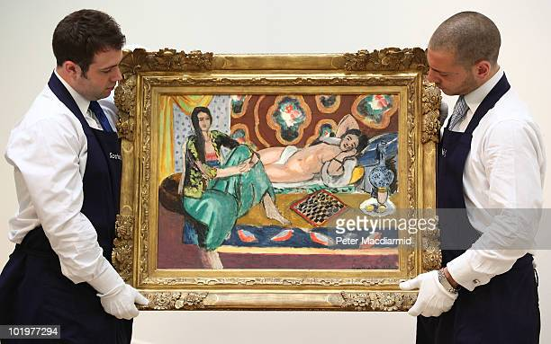 Sotheby's employees hold 'Odalisques jouant aux dames' by Henri Matisse on June 11, 2010 in London, England. The Matisse, estimated at £10-£15...