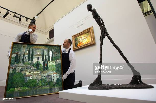 Sotheby's employees move a work entitled 'Kirche in Cassone' by Gustav Klimt at Sotheby's auction house on January 12 2010 in London England The...