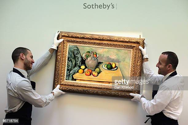 Sotheby's employees move a work entitled 'Pichet et fruits sur une table' by Paul Cézanne at Sotheby's auction house on January 12 2010 in London...