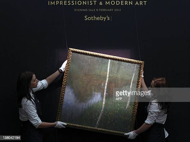 Sotheby's employees pose carrying Austrian painter Gustav Klimt's work entitled 'Seeufer mit Birken' painted in 1901 and expected to fetch between 6...