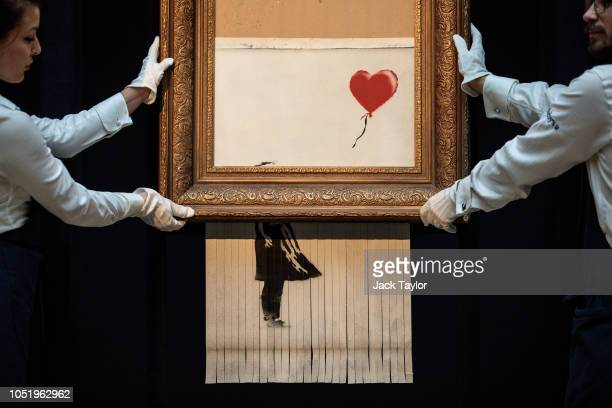 Sotheby's employees pose with 'Love is in the Bin' by British artist Banksy during a media preview at Sotheby's auction house on October 12 2018 in...
