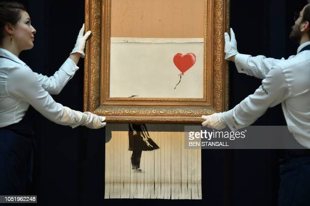 TOPSHOT Sotheby's employees pose with the newly completed work by artist Banksy entitled Love is in the Bin a work that was created when the painting...