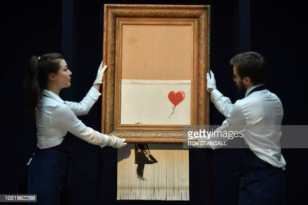 """Sotheby's employees pose with the newly completed work by artist Banksy entitled """"Love is in the Bin"""", a work that was created when the painting..."""